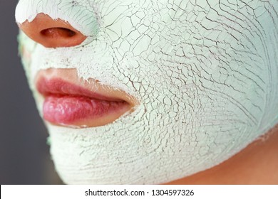 Close up woman with green white mud mask on face, detail view. Teen girl have dry cracked cosmetic on skin. Beauty treatment. Skincare.