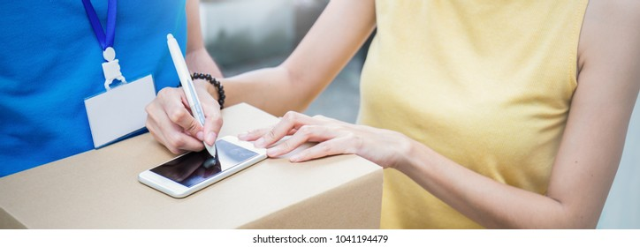 Close up woman hand appending receive sign signature after accepting a delivery of boxes from delivery man, sign and receive deliver e-commerce concept banner