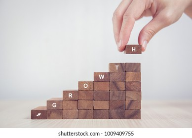Close up Woman hand arranging wood block stacking as step stair with GROWTH text. Business concept success process.