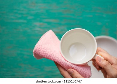 Close up woman hand cleaning coffee cup on the morning with microfiber cloth,Close up woman hand cleaning coffee cup on the rustic wood table.
