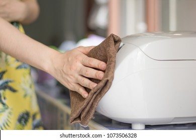 Close up woman hand cleaning rice cooker with cloth.