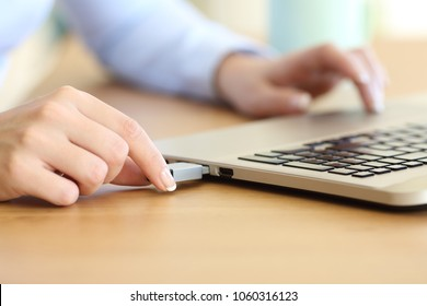 Close up of a woman hand connecting a pendrive in a laptop on a desktop