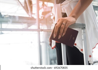 Close up of woman hand with engagement ring holding passport and suitcase, Travel concept
