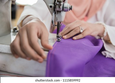 close up of woman hand fashion designer work using sewing machine in the office
