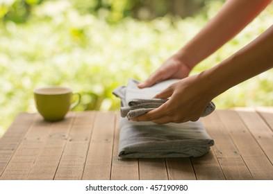 Close up woman hand folding clothes on wood table,Close up woman folding clothes into chest of drawers closeup.