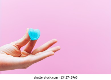 Close up of woman hand folding menstrual cup showing how to use, c form. Women health concept, zero waste alternatives. copy space