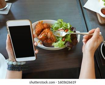 Close up of woman hand with fork for eating food and  lifestyle using or looking at his smartphone and having lunch in the restaurant with friends.