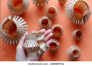 Close up woman hand hold three small lantern in palm and group of paper lanterns on orange background , popular ornamental for mid autumn season