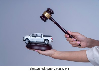 Close up of woman hand holding Auction hammer with golden a model car , Auction lawyers or notaries with gavel judge for the insurance compensations concept. Midsection of judge hitting car model.