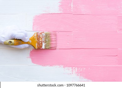 Close up woman hand holding brush painting pink color on a white wooden table