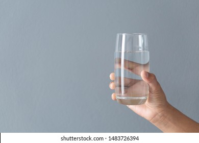 Close up woman hand holding a glass of pure water for dink with grey background, Health care concept