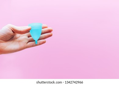 Close up of woman hand holding menstrual cup over pink background. Women health concept, zero waste alternatives. copy space