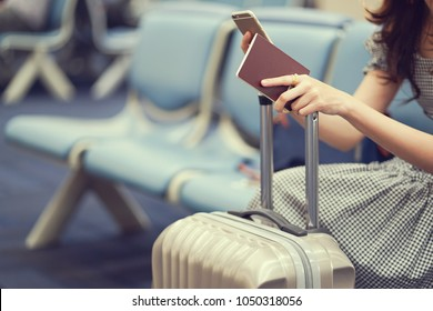 close up woman hand holding passport and playing smartphone on her suitcase at airport while waiting for boarding time ,traveler concept