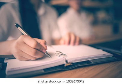 Close up of woman hand holding pen and writing on notebook,retre color design