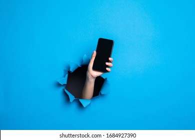 Close up of woman hand holding phone with screan for adv through blue hole in paper wall
