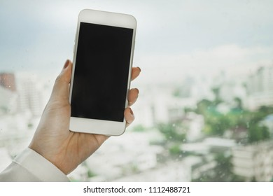 close up of woman hand holding smartphone on black screen with window and city view background.soft and selective focus
