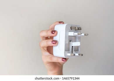 Close up of woman hand holding universal electric socket plug adapters, isolated on white background. Used to connect electrical outlets worldwide. Concept of solution, travel and technology.