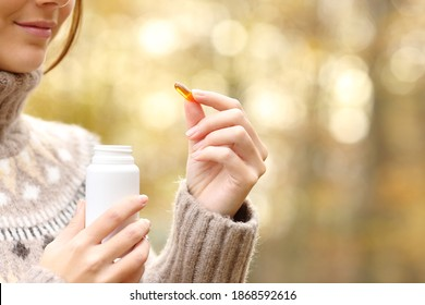 Close up of woman hand holding a vitamin pill and bottle in autumn in a forest