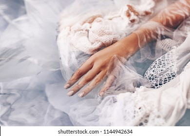 close up of woman hand lying in water with fabric. fashion concept