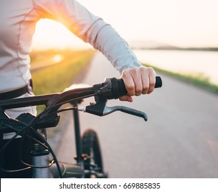 Close up woman hand on the bicycle handlebars