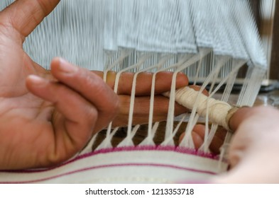 Close up of woman hand on weaving loom. She is weaving pink and white pattern on loom