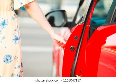 Close up  woman hand  opening red car door.