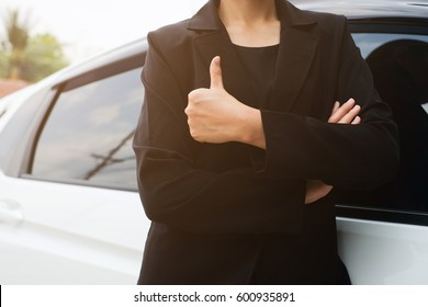 close up woman hand outstretched arms showing thumb up over car for make sure for safety and assurance of driving concept: