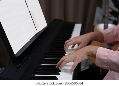 Close up woman hand playing piano at home. Relaxing time concept. Practicing music at home, White blank paper for note put on paino holder. Hands put on keyborad.