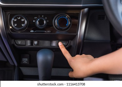Close up of woman hand pressing turn on air-conditioner button a car.