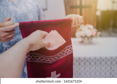 Close up of a woman hand putting tithing money into  offering bag  in front of  Pulpit at church
