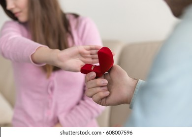 Close up of woman hand rejecting, turning down marriage proposal, engagement ring box, indoor. Asking to marry, requesting hand. Unpleasant surprise, bad birthday gift, disappointment in love, breakup