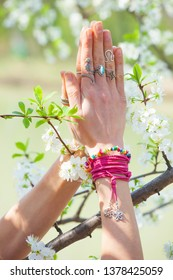 close up woman hand with rings and bracelets in yoga mudra namaste gesture in front cherry blossom