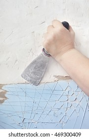 Close up of woman hand scraping wall with a spatula.
