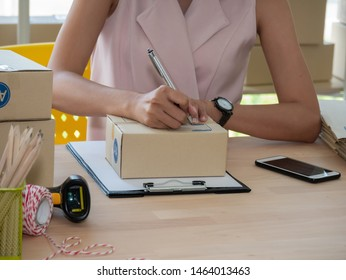 Close up of woman hand seller writing address on parcel box and checking product order on smartphone. Online women sellers working for e-business commerce. Shopping online, SME, freelance concept.