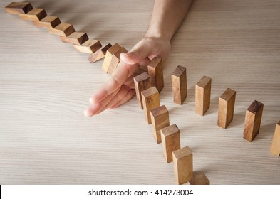 Close up woman hand stopping the domino wooden effect concept for business.