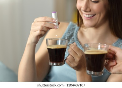 Close up of a woman hand throwing saccharine into a coffee cup sitting on a couch in the living room at home