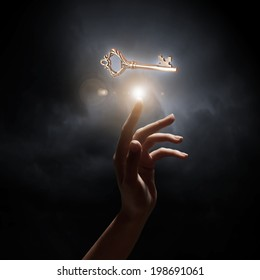 Close up of woman hand touching golden key