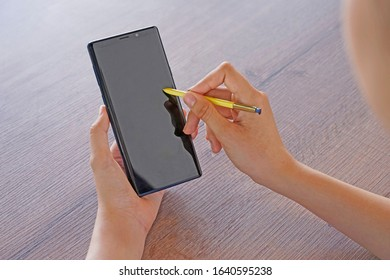 close up of woman hand using smart phone with stylus touch magic pen on the screen