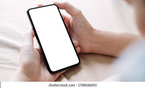 Nahaufnahme Hand der Frau Verwendung eines Smartphones mit weißem Bildschirm zu Hause.