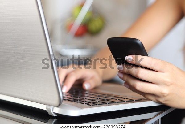 Close up of a woman hand using a smart phone and typing a laptop in the kitchen at home