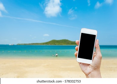 Close up of woman hand using white smart phone on the beach with blue sky background. Girl holding mobile phone on natural background