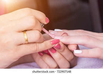Close up woman hand while process of manicure in nail shop. Beautiful concept.