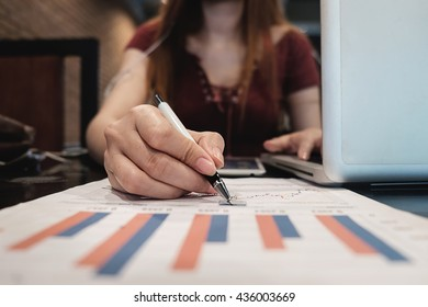 close up of woman hand working on laptop computer with business graph information diagram on desk as concept