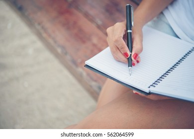 Close up of woman hand writing on notepad.