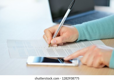 Close up of a woman hand writing or signing in a document on consulting a mobile phone on a desk at home or office