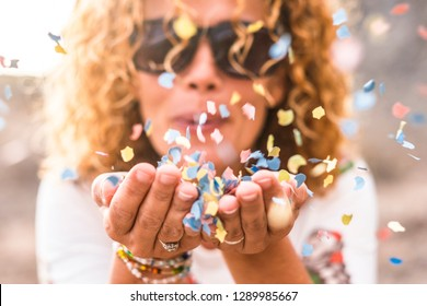 Close up of woman hands and beautiful lady blowing out coloured carnival party confetti - focus on colors papers and happiness and joyful lifestyle concept for happy people outdoor