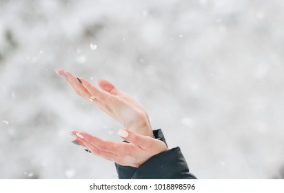 Close up of woman hands catching the snowflakes,winter photo