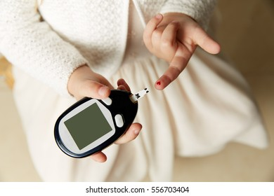 close up of woman hands checking blood sugar level by Glucose meter on white background - Medicine, diabetes, glycemia, health care and people concept