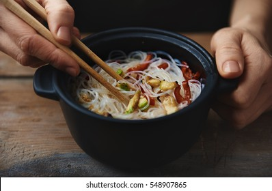 Close up of woman hands with chopsticks eating chinese noodles at wooden table.