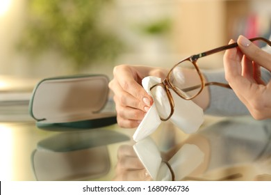 Close up of woman hands cleaning glasses with tissue paper on a desk at home